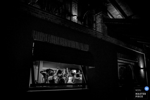 The bride and guests can be seen celebrating inside the reception hall from outside at night in this black and white image captured by a Piedmont wedding photographer.
