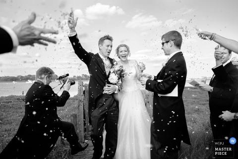 Gäste werfen dem Brautpaar Konfetti zu, wenn sie die Zeremonie im Freien in diesem Schwarzweißfoto verlassen, das von einem Hochzeitsreportagefotografen aus Dorset, England, aufgenommen wurde.