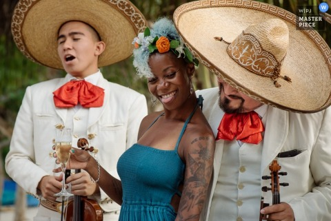 A woman dances with the mariachi band as she holds a glass of champagne in this photo by a Cartago, Costa Rica wedding photographer.
