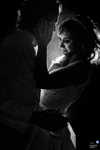 The bride puts her hand on the groom's face as they dance together during the reception in this black and white image by a Sao Paulo documentary wedding photographer.