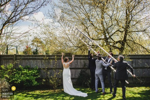 A bride directs four men as they try to place a ladder in this documentary-style photo captured by a Derbyshire wedding photographer.