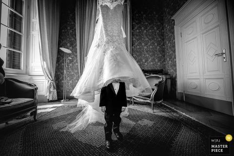 Czarno-białe zdjęcie młodego chłopca z głową w sukni panny młodej, która wisi na suficie przez fotografa ślubnego z Lombardii.