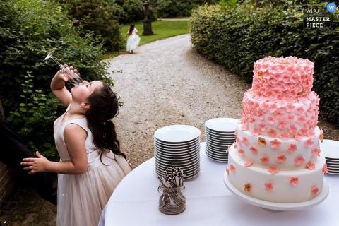 Une fille boit un verre de champagne devant le gâteau de mariage sur cette photo composée par un photographe de mariage de Rotterdam.
