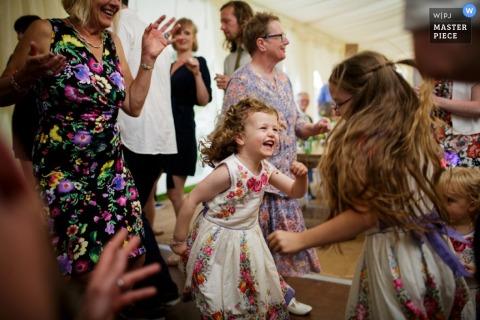 Zwei kleine Mädchen tanzen herum, während die Gäste auf diesem Foto von einem preisgekrönten Hochzeitsfotografen aus Jersey, den Kanalinseln, zusehen.