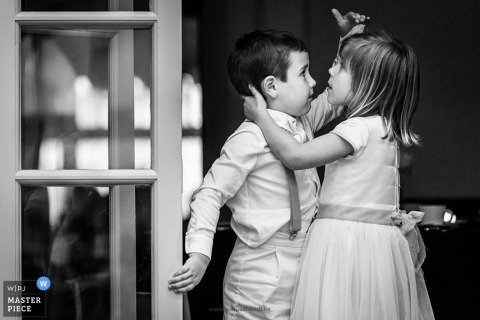 Black and white photo of a young boy and girl comparing heights by an Antwerpen wedding photographer.