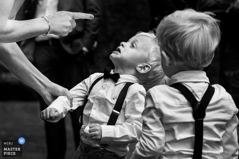 A woman shakes her finger at a little boy in this black and white photo by an award-winning Antwerpen wedding photographer.