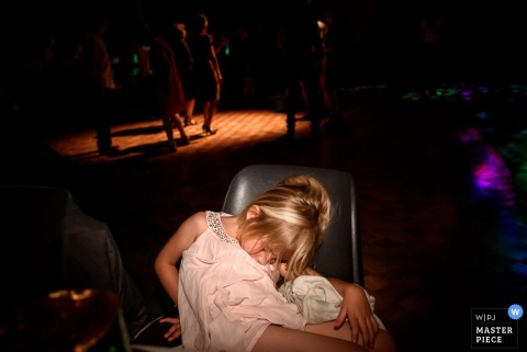 A little girl sleeps slumped in a chair while guests dance on the dance floor in this wedding photo by a Nantes photographer.