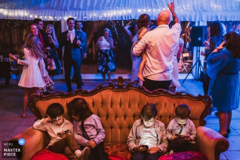 Children sit on a couch playing with mobile devices while guests dance behind them in this wedding reception photo captured by an award-winning New South Wales, Australia photographer.