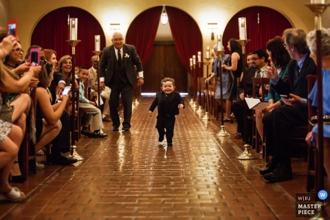 A little boy runs excitedly down the aisle in this wedding photo taken by a San Francisco, CA photographer.