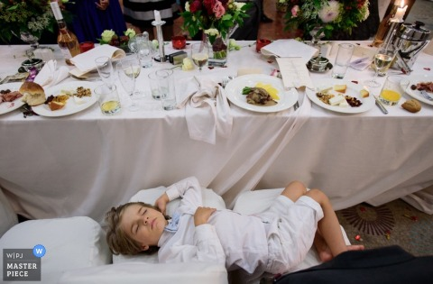 Photo of a young boy sleeping on chairs in front of a table of dinner plates at the reception by a Sofia, Bulgaria wedding photographer.