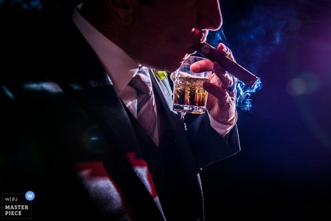 Photo of a man smoking a cigar while he holds his drink in the same hand by a Boulder, CO wedding photographer.