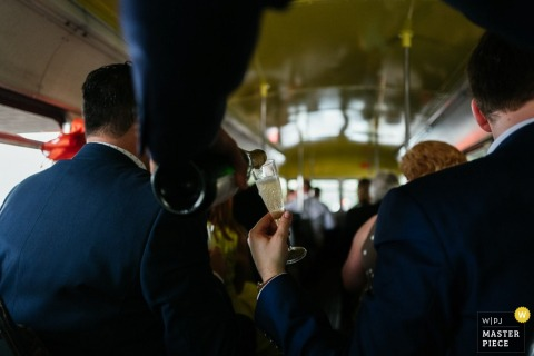 A man pours champagne into another man's glass as the bridal party rides on a bus in this wedding photo taken by a London England reportage photographer.