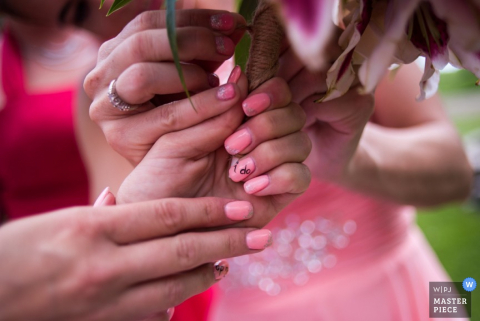 Detail photo of two women holding a bouquet. Captured by an Omaha, NE documentary wedding photographer.