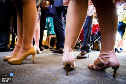 Detail photo of guests shoes as they gather for the reception. Taken by a Hertfordshire, England wedding reportage photographer.