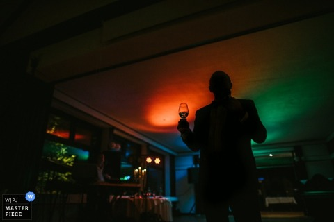 Photo of a silhouette of a man holding a glass of champagne by a Lower Saxony, Germany wedding photographer.