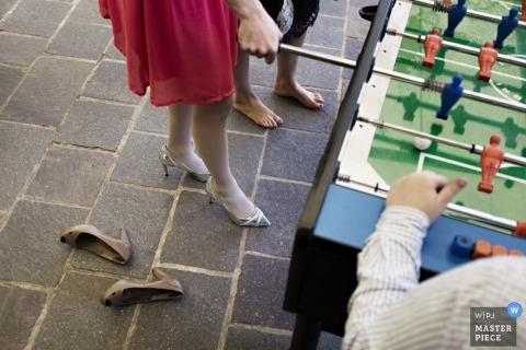 Detalle la foto de los pies de los invitados mientras juegan un juego de futbolín. Capturado por un fotógrafo de bodas galardonado en Lombardía.