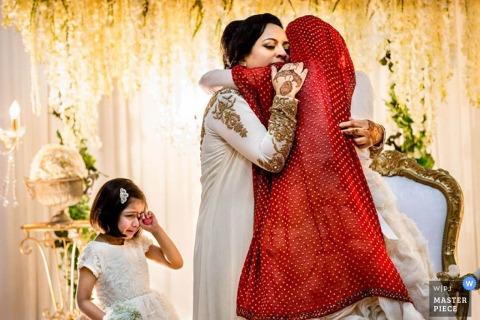 Een vrouw knuffelt de bruid terwijl een jong meisje op deze foto kijkt door een fotograaf van een trouwreportage uit Devon, Engeland.