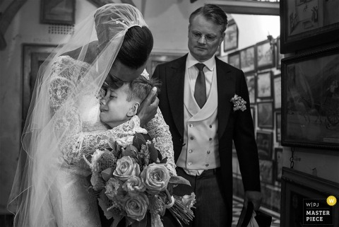 The bride hugs a little boy in this black and white image captured by a Tuscany wedding photographer.
