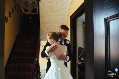 A father hugs the bride before the ceremony in this picture recorded by a London, England wedding reportage photographer.