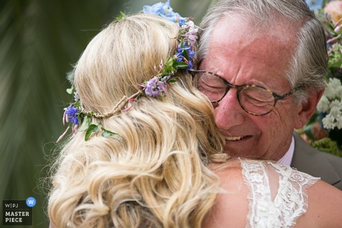 Photo of the bride hugging her father by a San Francisco, CA wedding photographer.