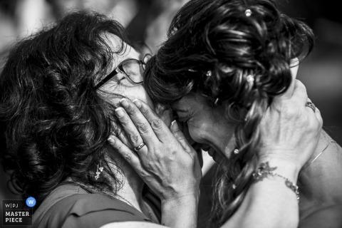 Zwart-witte foto van een vrouw die het voorhoofd van de bruid kust door een het huwelijksfotograaf van Lombardije.