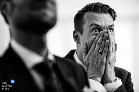 A man covers his face with his hands in amazement in this black and white photo by a Hertfordshire, England wedding reportage photographer.