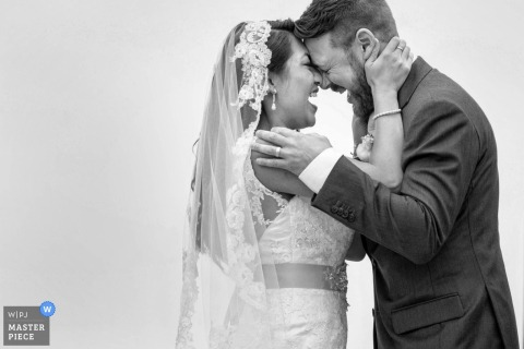 A bride and groom hold each other and laugh in this black and white image composed by an award-winning San Diego, CA wedding photographer.