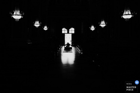 Black and white photo of the aisle hidden mostly in shadow with lights overhead by a Modena wedding photographer.
