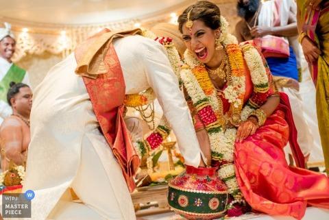 La novia se ríe mientras ella y el novio alcanzan una olla durante la ceremonia en esta foto de un fotógrafo de reportajes de bodas en Essex, Inglaterra.
