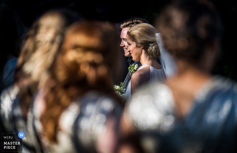 La mariée et le marié peuvent être vus à travers un groupe d'invités alors qu'ils sortent de la cérémonie dans cette photo de mariage enregistrée par un photographe de Charlotte, Caroline du Nord.