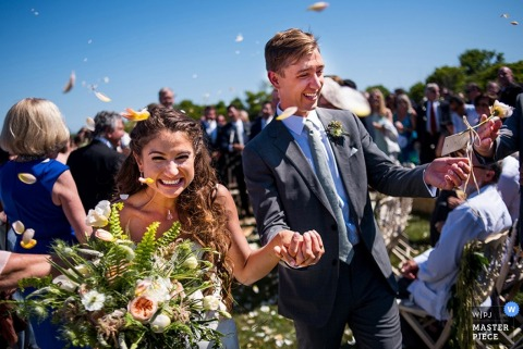 The bride and groom hold hands as guests toss flower petals in this photo by an Atlanta, GA wedding photographer.