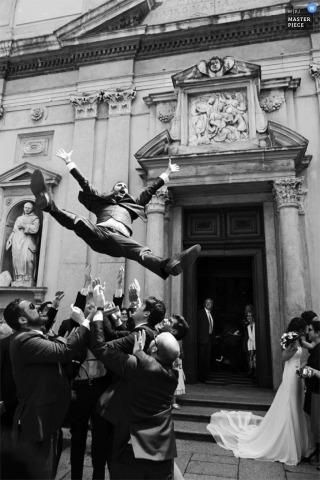 Los padrinos de boda lanzan al novio al aire fuera de la iglesia después de la ceremonia en esta imagen en blanco y negro compuesta por un fotógrafo de bodas de Lombardía.