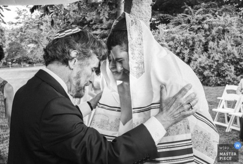 Black and white photo of the groom and rabbi during the ceremony by a Brooklyn, NY wedding photographer.