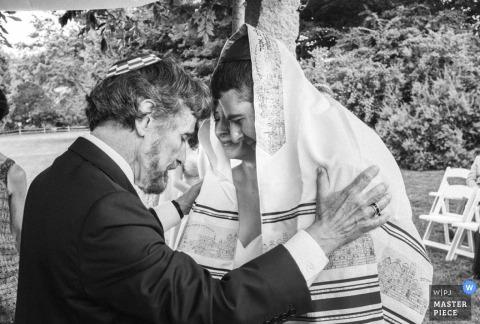 Foto in bianco e nero dello sposo e rabbino durante la cerimonia da un fotografo di matrimoni di Brooklyn, New York.