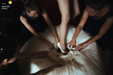 Three bridesmaids help the bride step into her dress in this photo by a London, England wedding reportage photographer.