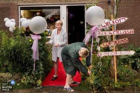 Foto van een man en een vrouw die de buitenkant van de feestzaal decoreren door een Nederlandse trouwfotograaf.