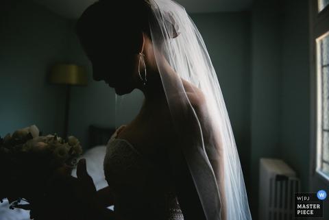 Panna młoda stoi w swoim pokoju, patrząc na bukiet w swoich rękach na tym zdjęciu francuskiego fotografa ślubnego.
