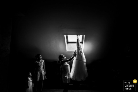 A woman examines the bride's gown as it hangs in a skylight in this black and white photo by a Piedmont wedding photographer.