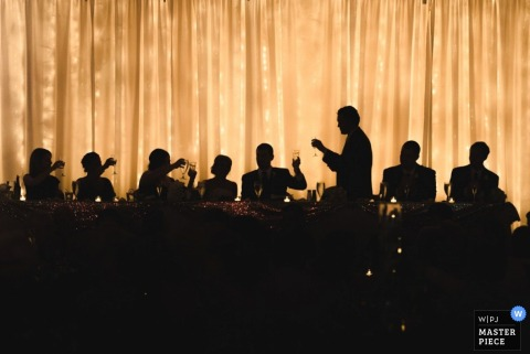 Guests are silhouetted as they sit at a long table and toast the bride and groom in this wedding photo composed by a Cleveland, OH documentary photographer.