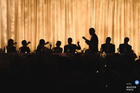 Gasten worden gesilhouetteerd terwijl ze aan een lange tafel zitten en toost de bruid en bruidegom in deze trouwfoto, gecomponeerd door een Cleveland, OH documentaire fotograaf.