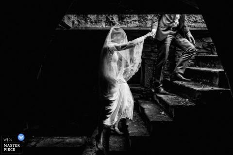 De bruidegom neemt de hand van de bruid terwijl ze samen de trap op lopen in deze zwart-witfoto gecomponeerd door een huwelijksfotograaf uit Montpellier.