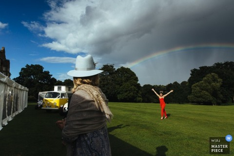 A woman runs beneath a rainbow outside in this photo captured by a London, England wedding reportage photographer.