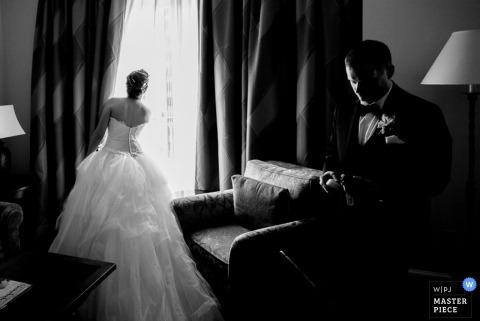 Schwarzweiss-Foto der Braut, die heraus ein Fenster als der Bräutigam schaut, überprüft seine Uhr von einem Hochzeitsfotografen San Antonio, TX.