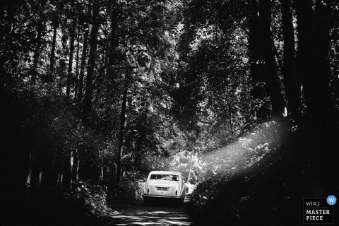 Black and white photo of a white car driving on a narrow road through the woods by a Scotland wedding reportage photographer.
