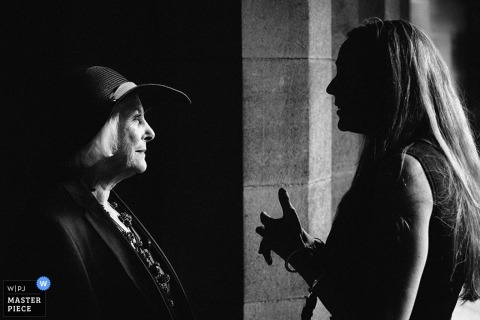 Two women speak with each other in this black and white photo by an award-winning Scotland wedding reportage photographer.