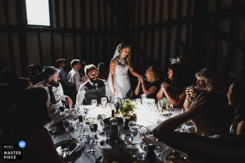 The bride stands and speaks to guests at her table in this wedding photo captured by a Derbyshire documentary photographer.