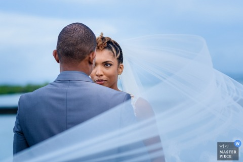 Photo of the bride and groom as the bride's veil blows around him by a Martinique wedding photographer.