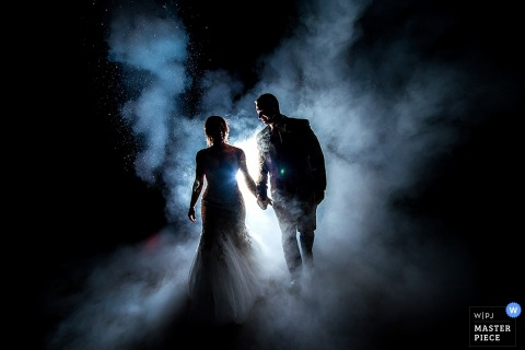 Portrait of the bride and groom surrounded by fog as they hold hands and a bright light shines through by a Boulder, CO wedding photographer.
