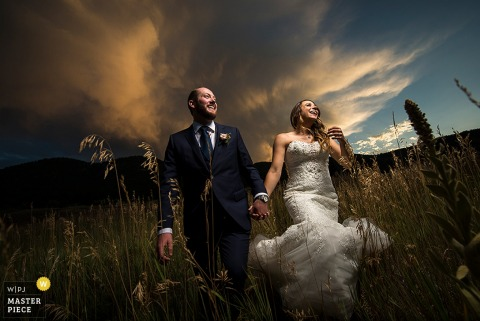 Photo of the bride and groom walking through a field of tall grass holding hands at dusk by a Boulder, CO wedding photographer.