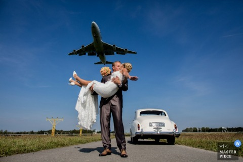 The groom picks up his bride and kisses her as an airplane flies overhead in this photo by a Netherlands wedding photographer.